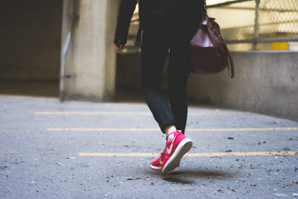 femme portant un blouson noir un pantalon noir et des baskets rouges