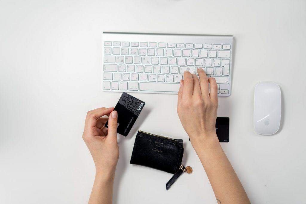 personne qui tape sur un clavier d'une main et qui tient sa carte bancaire de l'autre